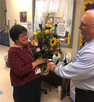 Nurse accepting flowers from Superintendent