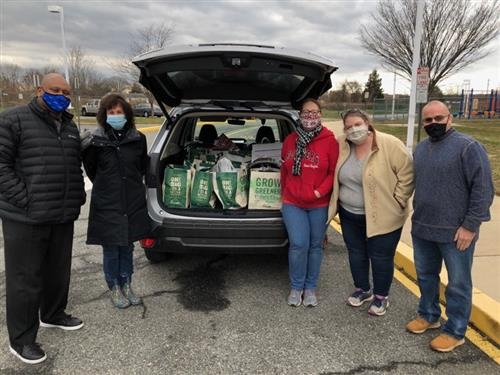 Donations from Quota International of Wilmington, DE. 5 people standing behind a car with the hatch open.