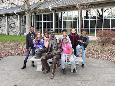 Group of Leasure Elementary Students at Gettysburg standing around a statue of Abraham Lincoln