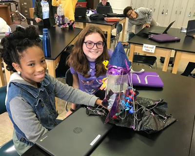 Two female students in the Middle School Honors Program showing off their rocket