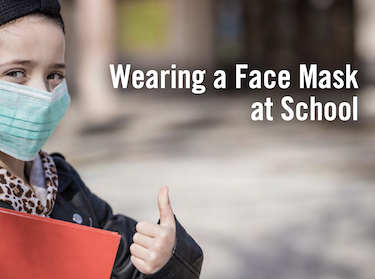 a young child wearing a face mask standing outside of a school with her thumb up