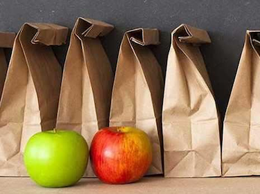 brown paper lunch bags lined up in a row with a red apple and green apple in front of them
