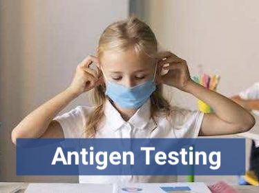 Student sitting at desk with face mask with the words 'antigen testing' overlay