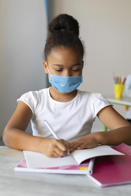 little-girl-writing-notebook-while-wearing-medical-mask