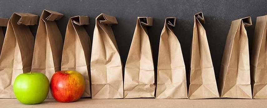 A row of prepacked school lunches in brown paper bags.