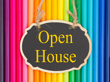 Open House sign. colored pencils in the background.